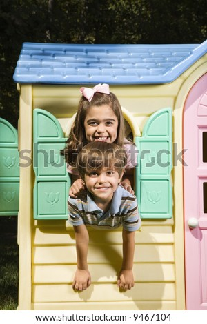 Hispanic boy and girl posing in window of playhouse and smiling at viewer. - stock photo