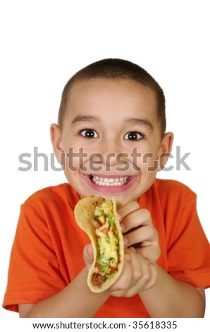 Hispanic boy holding a Mexican-style taco, focus is on model's face - stock photo