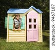 Hispanic boy in window of outdoor playhouse smiling at viewer. - stock photo