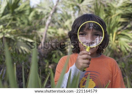 Hispanic boy looking through magnifying glass - stock photo