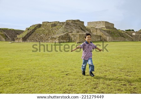 Hispanic boy running in front of ruins, Oaxaca, Mexico - stock photo