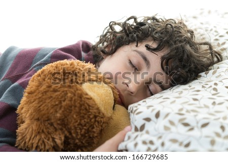 Hispanic boy sleeping quietly while holding his preferred toy - stock photo