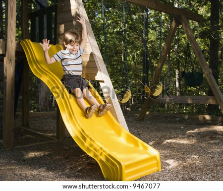 Hispanic boy sliding down outdoor slide with arms raised above head. - stock photo