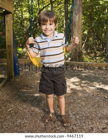 Hispanic boy standing by swing set smiling at viewer.