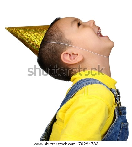 Hispanic boy with party hat looking up, laughing, four years old, isolated on pure white background - stock photo