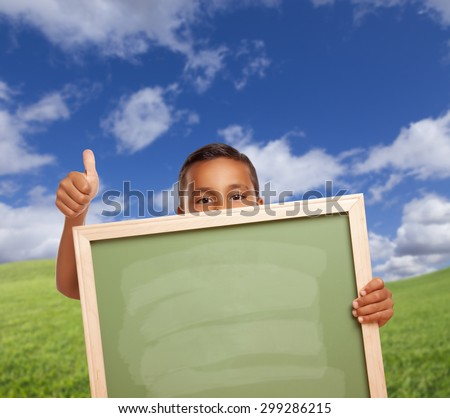 Hispanic Boy with Thumbs Up in Grass Field Holding Blank Chalk Board. - stock photo