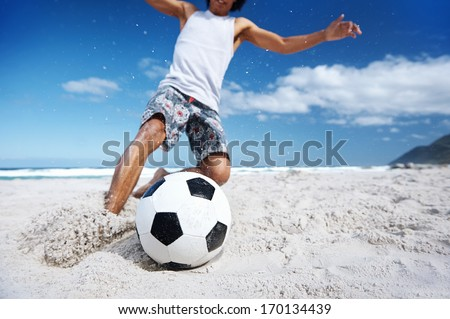 Hispanic Brasil man playing soccer on beach with dribble skill and ball on vacation - stock photo