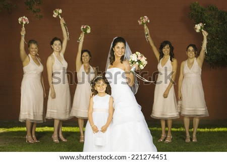 Hispanic bride and bridesmaids holding bouquets - stock photo