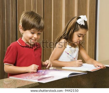 Hispanic brother and sister doing homework. - stock photo