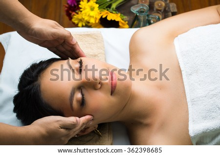 Hispanic brunette model getting massage spa treatment, hands working on massaging womans head and face with eyes closed - stock photo