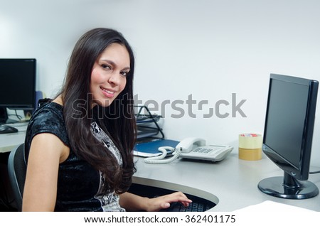 Hispanic brunette office woman sitting by desk and working on computer with positive attitude smiling