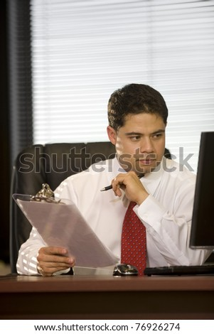 Hispanic Business Man Looking at Computer in the Office