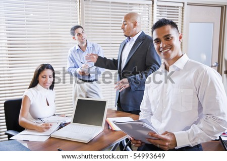 Hispanic business manager meeting with office workers, focus on man in foreground