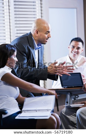 Hispanic business manager meeting with office workers, giving directions - stock photo