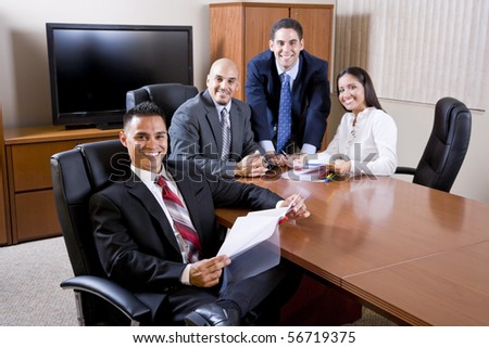 Hispanic business people meeting in boardroom, focus on man in foreground - stock photo