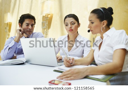 Hispanic business people using laptop together in office