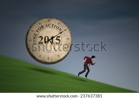 Hispanic business person runs down from the hill with a clock chasing him