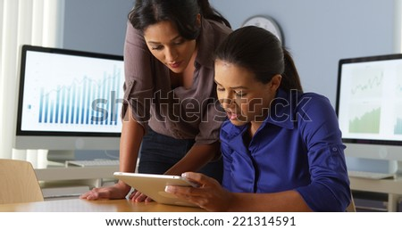 Hispanic business women working with colleague on tablet computer - stock photo