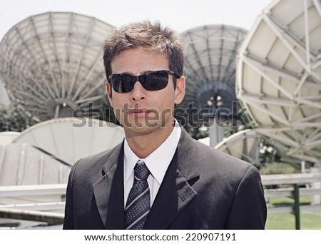Hispanic businessman in front of satellite dishes - stock photo