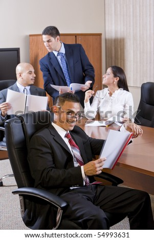 Hispanic businessman in meeting reviewing report, colleagues discussing - stock photo