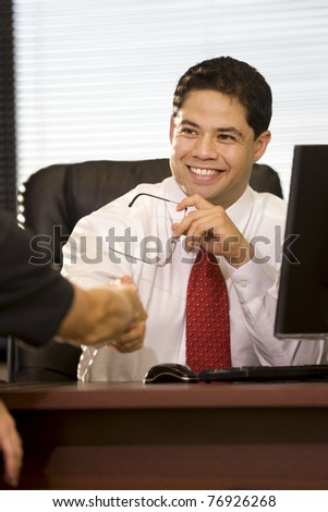 Hispanic Businessman Shaking Hands in the Office - stock photo