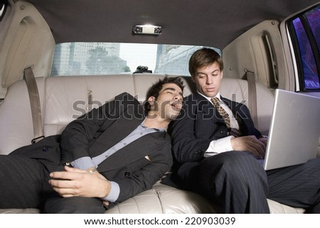 Hispanic businessman sleeping on coworker in limousine - stock photo