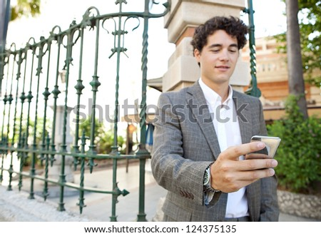 Hispanic businessman using a smart phone while standing in the corner of a classic city street. - stock photo