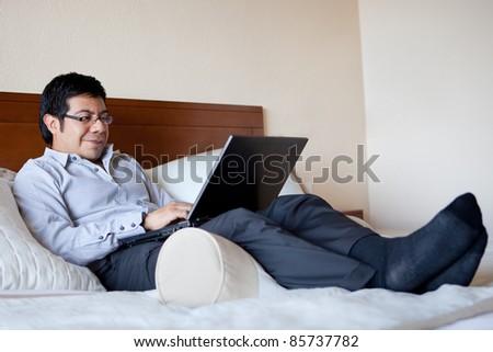 Hispanic businessman using laptop in his hotel room - stock photo