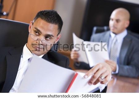 Hispanic businessmen in boardroom reviewing report, watching presentation - stock photo