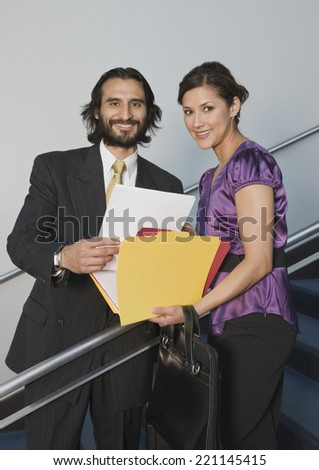 Hispanic businesspeople holding folders