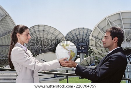 Hispanic businesspeople holding globe in front of satellite dishes - stock photo