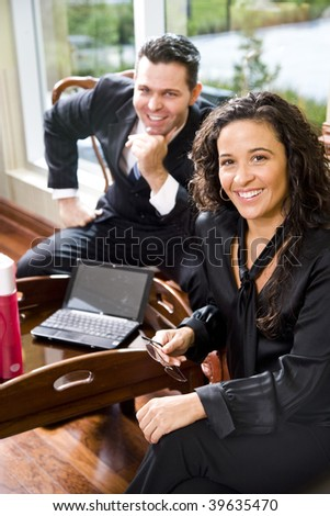 Hispanic businesswoman in office working with male colleague, focus on foreground - stock photo