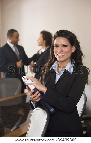 Hispanic businesswoman standing in boardroom, colleagues in background - stock photo