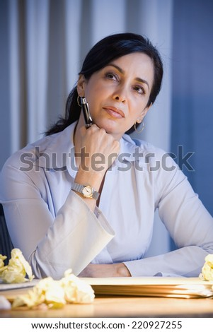 Hispanic businesswoman thinking