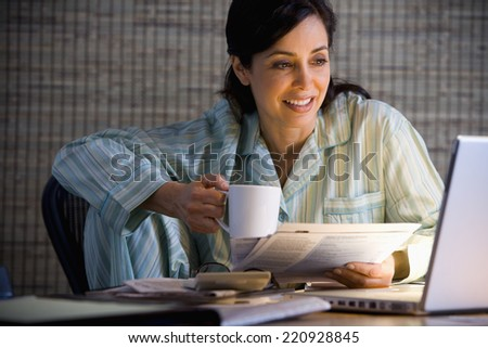 Hispanic businesswoman working in pajamas - stock photo