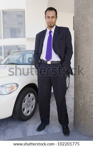 Hispanic car salesman next to new car - stock photo