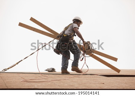 Hispanic carpenter carrying studs and pneumatic air gun on roof of new home under construction while wearing a safety harness  - stock photo