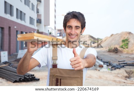 Hispanic carpenter on construction site showing thumb - stock photo