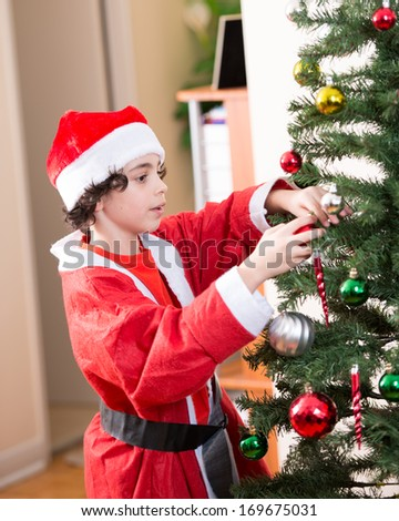 Hispanic child having fun and enjoying while putting together a Christmas tree at home. Boy dressed for Christmas