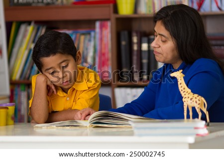 Hispanic Child Learning to Read with Mom