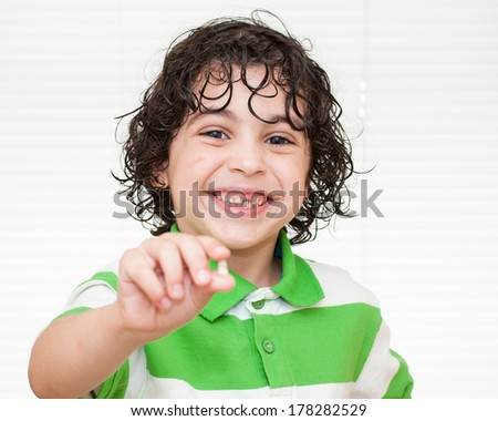 Hispanic child showing the first milk tooth he lost.