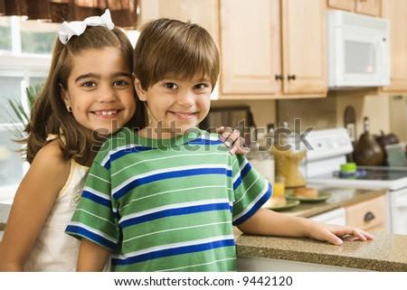 Hispanic children in kitchen smiling at viewer. - stock photo