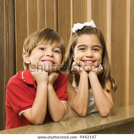 Hispanic children with their head on hands smiling at viewer. - stock photo