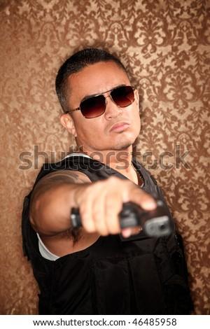 Hispanic Cop Pointing Gun at Camera Gangster Style - stock photo
