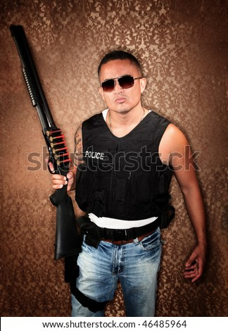 Hispanic Cop Wearing Bulletproof Vest and Holding Shotgun - stock photo
