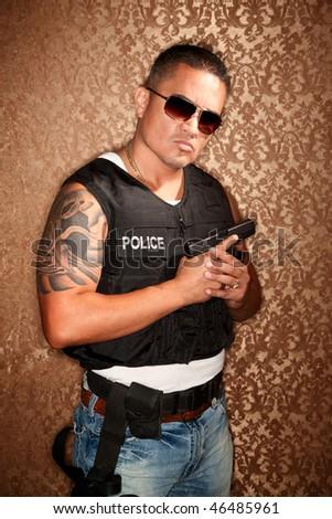 Hispanic Cop Wearing Bulletproof Vest and Holding Small Gun - stock photo