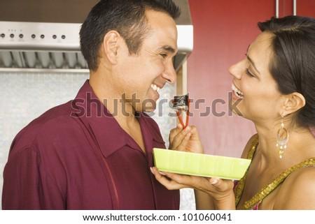 Hispanic couple eating sushi in kitchen - stock photo