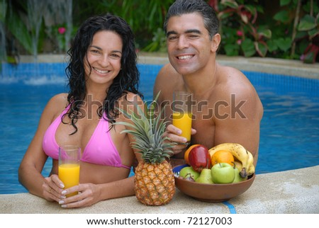 Hispanic couple eating tropical fruit in a swimming pool. - stock photo