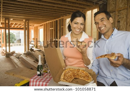 Hispanic couple having pizza and champagne at construction site - stock photo