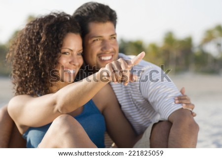 Hispanic couple hugging and pointing